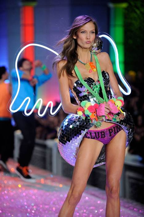 Description: Newly minted Angel Karlie Kloss wears the show's closing look, which features white neon-lined cartoon win gs and a disco-ball bustle.