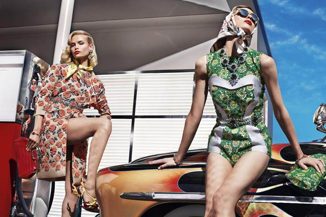 Description: Prada: Lace coats, bathing suits, sexy bandeau tops and leather pencil skirts combined with crystal jewels and automotive inconography from the '50s for a ladylike look with a smouldering edge.