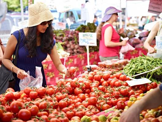 Description: Shoppers pick through the fruits and vegetables at a local farmers market