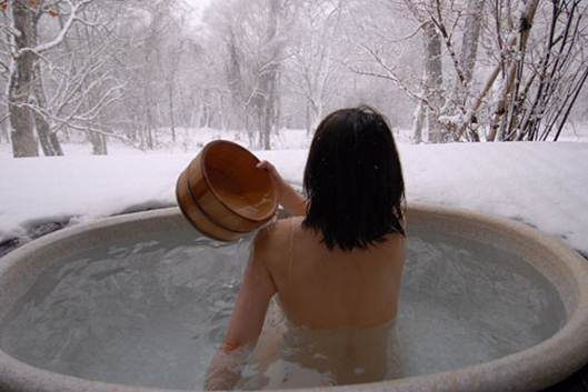 Description: A woman enjoying open air onsen in Hokkaido