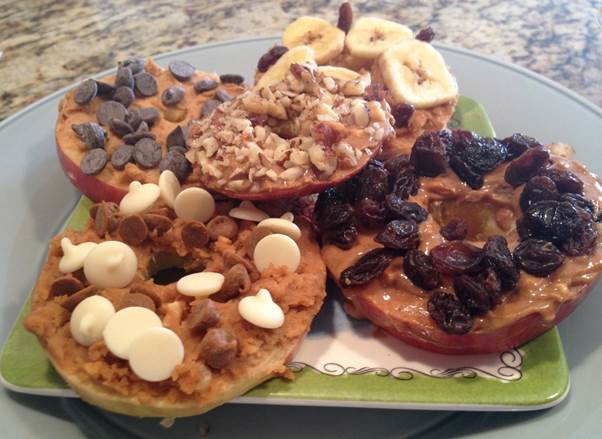 Apple slices dipped in peanut butter and chopped nuts