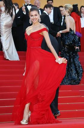 Description: Irina Shayk Rusian beauty showing off her glossy bare legs in red thigh-cut dress