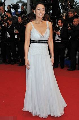 Description: Gong Li looking young at the age of forty in white dress with a deep cut at the chest showing plump bosom