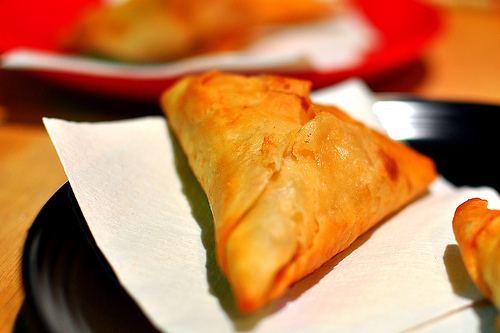 Description: Sambusas, The triangular parcels were filled with fried beef, green peppers, jalapenos, and onions.