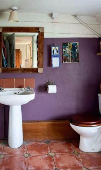 Description: Bathroom - Carola updated the room by painting the wall in a deliciously dark purple, which works well with the warm wood and terracotta tones