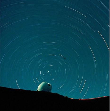 Description: Stars form arcs around the North Star above the Mauna Kea Observatory, Hawaii