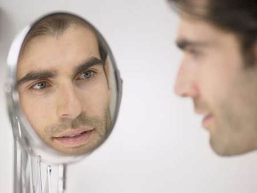 Description: Men are looking in the mirror and these first grey hairs are appearing
